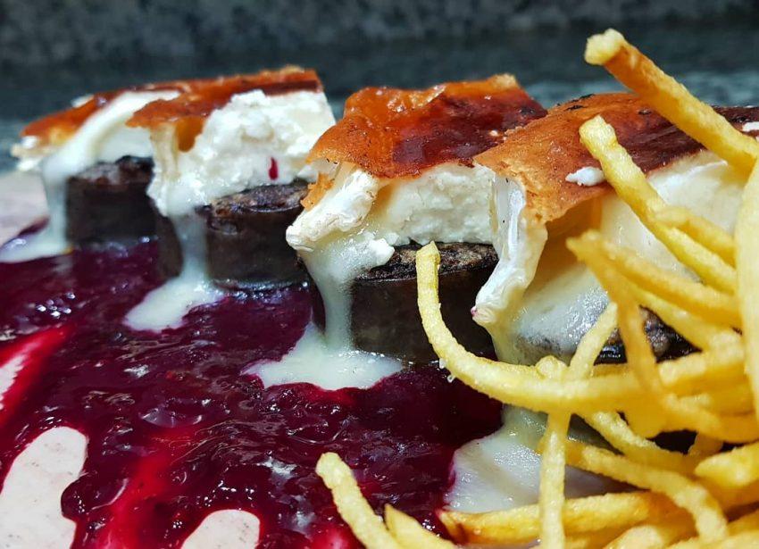Monedas de morcilla con queso de cabra y chutney de frutos rojos